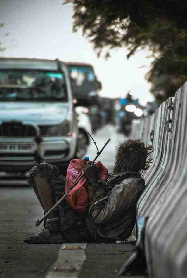 man sitting at the side of the road